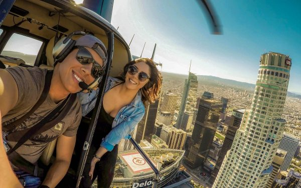 Young couple enjoy helicopter tour over Downtown